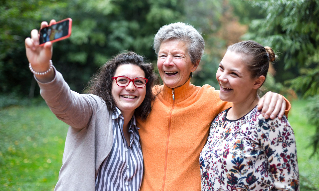 Two women taking a selfie with an older woman